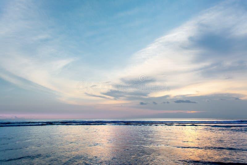 Härlig pastellfärgad solnedgång eller soluppgång på stranden med solljusreflexion på yttersida för havsvatten Linsformad cirrusmo arkivfoto