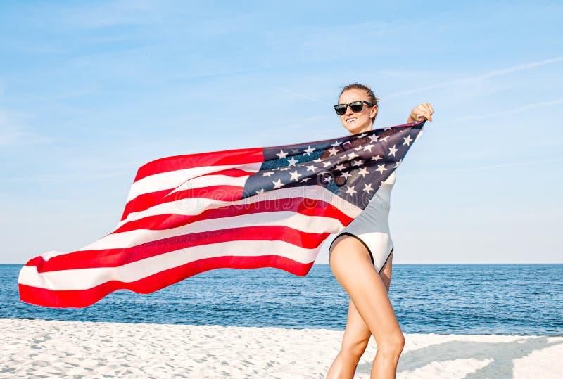 Härlig patriotisk kvinna som rymmer en amerikanska flaggan på stranden USA självständighetsdagen, 4th Juli fotografering för bildbyråer