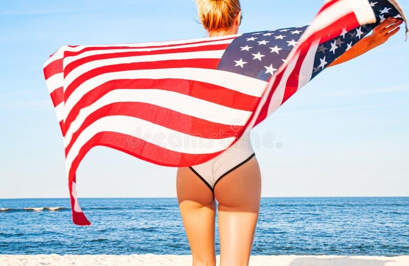 Härlig patriotisk kvinna som rymmer en amerikanska flaggan på stranden USA självständighetsdagen, 4th Juli svart isolerad begrepp royaltyfri fotografi