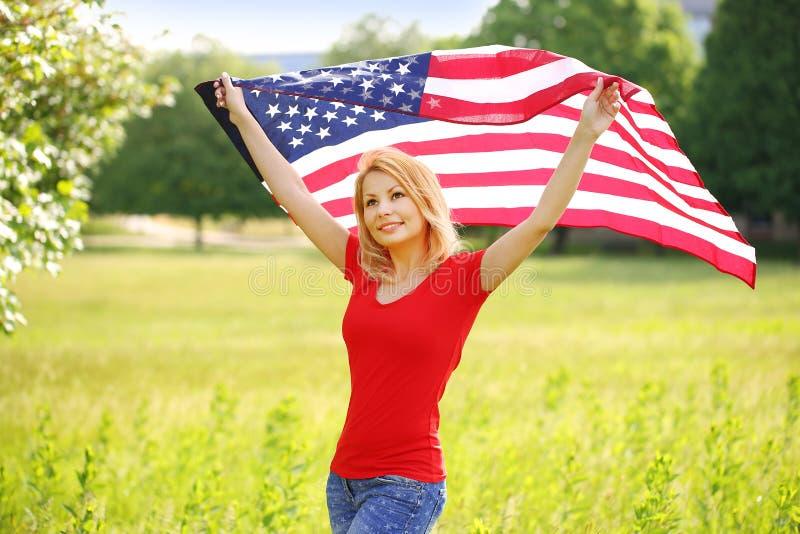 Härlig patriotisk ung kvinna med amerikanska flaggan arkivbild