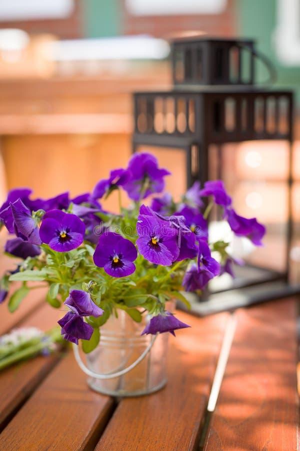 Härlig pensé i en metallhink som en tabellinställningsgarnering Nice blommor och en lykta på trätabellen utomhus arkivfoton