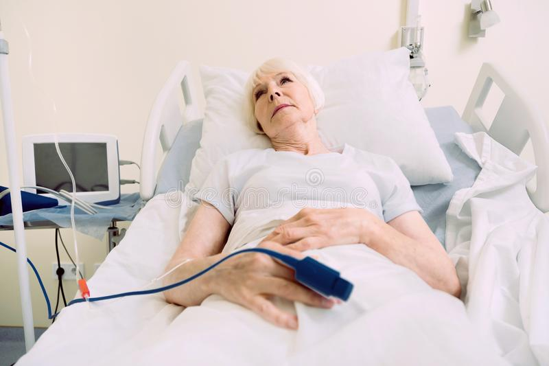 Härlig pensionerad dam som ligger i säng med pulsoximeteren royaltyfria foton