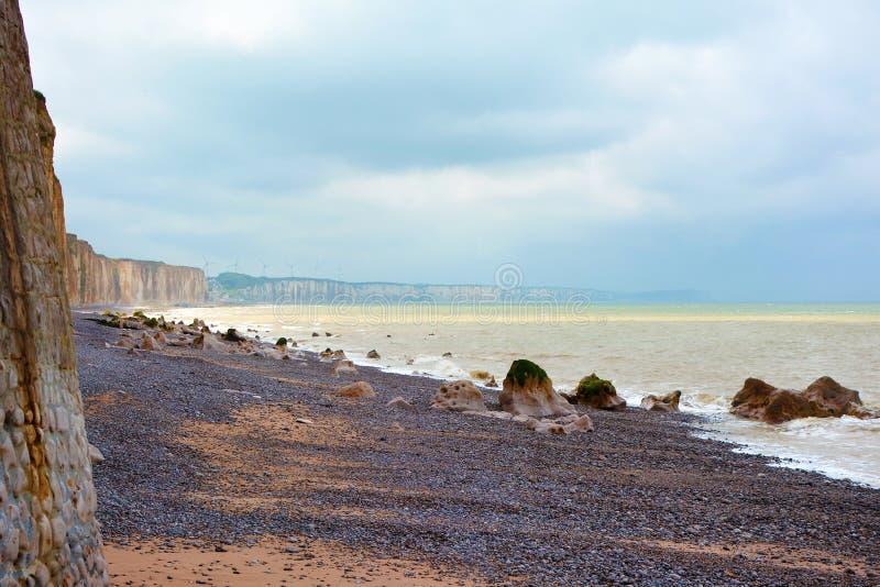 Härlig peppelstrand, hav med guld- ljusa reflexioner och kritaklippor i avlägset avstånd i Normandie, Frankrike royaltyfri fotografi