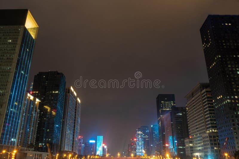 Härlig plats av upplyst ljus av kontorsbyggnader i affärsområde på bakgrund för natthimmel fotografering för bildbyråer