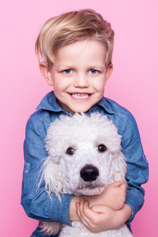 Härlig pojke med den kungliga standarda pudeln Studiostående över rosa bakgrund Begrepp: kamratskap mellan pojken och hans hund arkivfoto