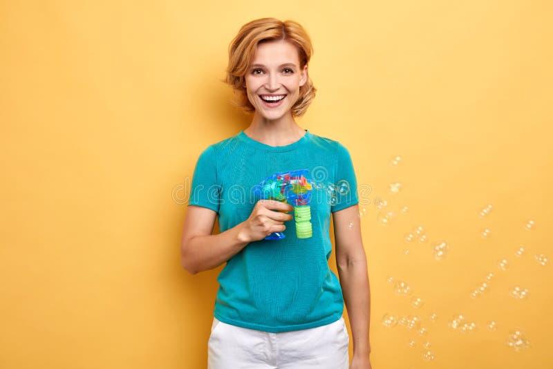 Härlig positiv flicka i den blåa T-tröja som gör såpbubblor arkivfoto