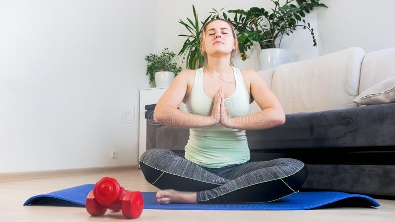 Härlig praktiserande yoga för ung kvinna i vardagsrum hemma arkivbilder