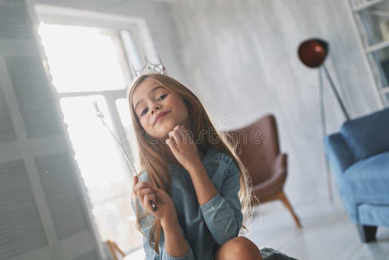 härlig princess Prideful liten flicka som håller handen på hakan royaltyfri bild