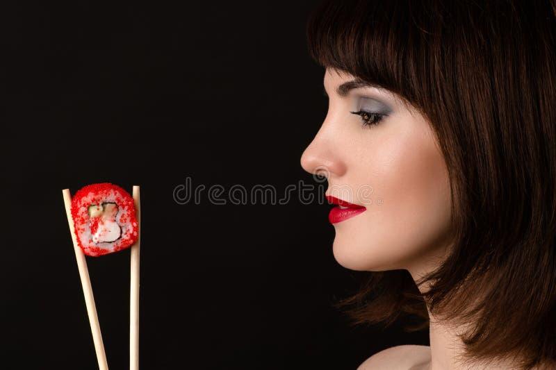 Härlig profilframsidakvinna med pinnar och rulle royaltyfri foto