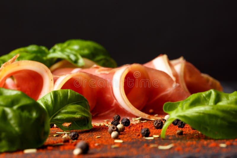 Härlig prosciutto med gröna spenatsidor Klipp jamon med peppar på en svart bakgrund läcker meat Restaurang arkivfoton