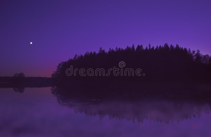 Härlig purpurfärgad solnedgång vid sjön i sommar, med månen som skiner arkivbilder