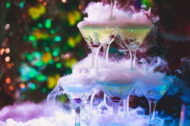 Härlig pyramidlinje av olika färgade alkoholcoctailar med mintkaramellen på julpartiet, tequila, martini, vodka och andra nolla royaltyfri foto
