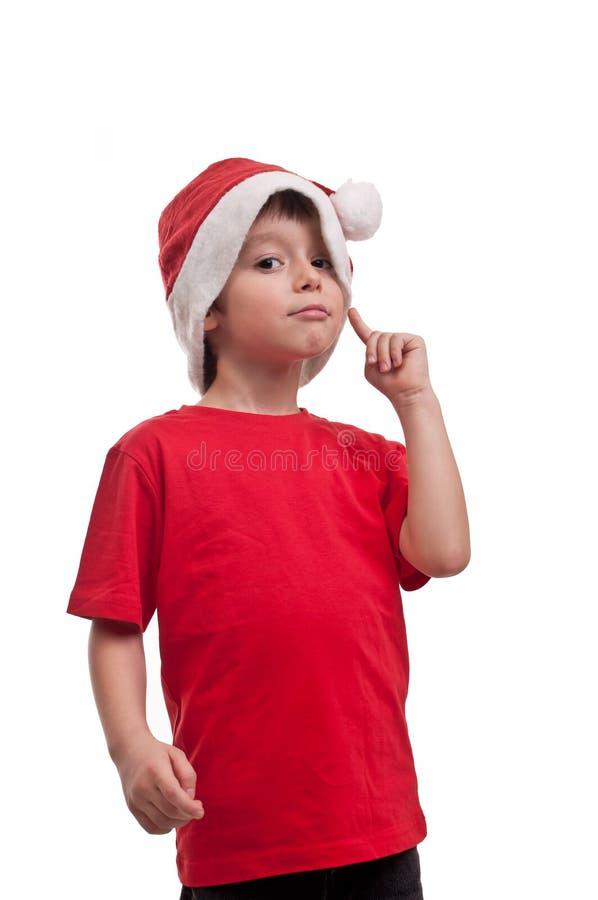 Härlig pys i hatt av Santa Claus med fingret på hans kind som isoleras på vit bakgrund arkivbild