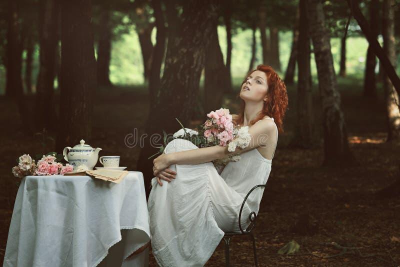 Härlig röd hårkvinna i en skog arkivbilder