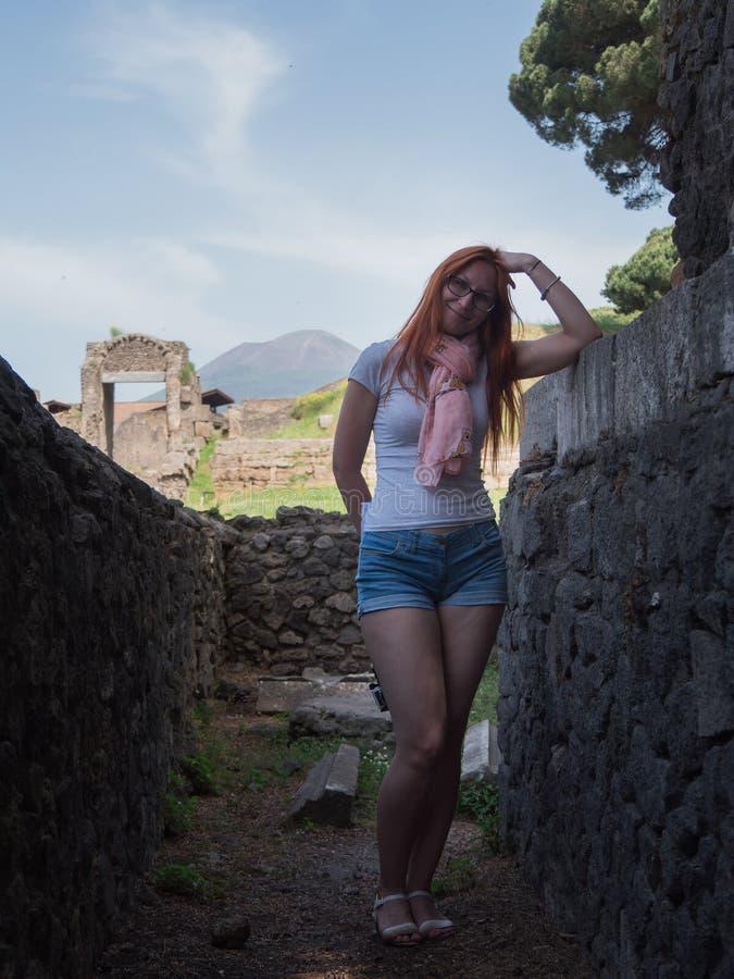 Härlig röd hårkvinna i exponeringsglas och kortslutningar som står i pompeii, Italien - varm sommarmiddag arkivfoton