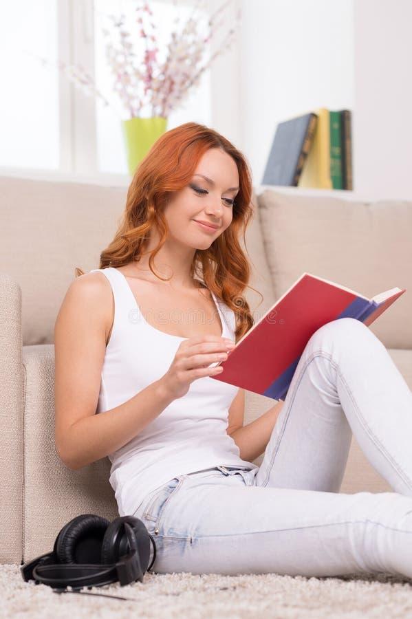 Härlig röd hårkvinnaläsebok  royaltyfri fotografi