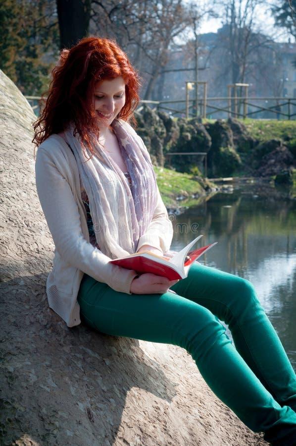 Härlig röd head läsebok för ung kvinna arkivfoto