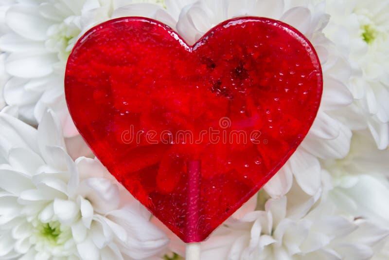 Härlig röd hjärta formade godisen i bakgrund för vita blommor arkivfoto