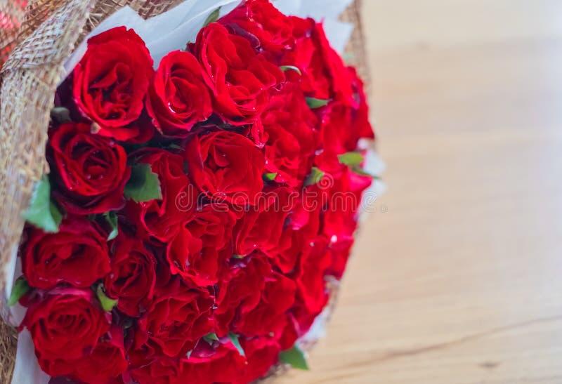 Härlig röd rosbukett på den wood tabellen royaltyfria foton