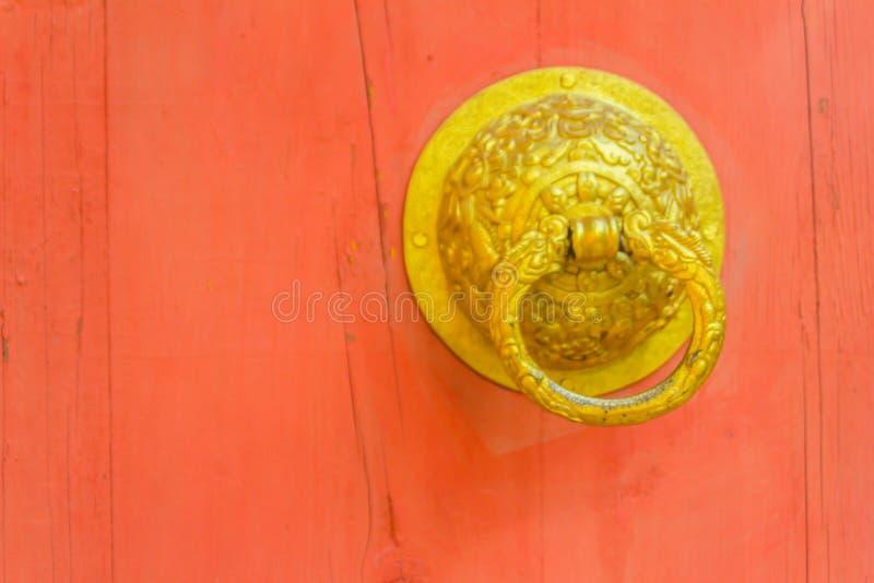 Härlig röd trädörr till Bhutan stilbakgrund med dörrknoppen av guld- metall på den offentliga templet arkivbilder