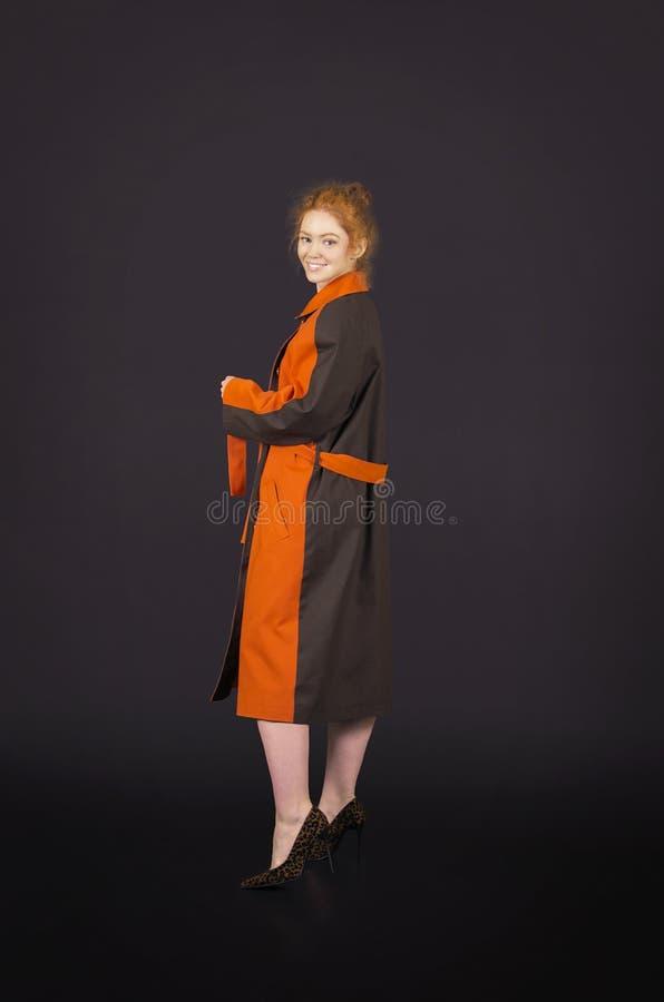 Härlig rödhårig flicka i orange posera för kappa arkivfoto