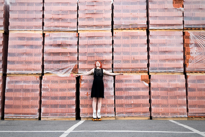 Härlig rödhårig flicka i svart klänning på rullskridskorstandi arkivbilder