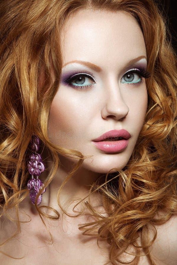 Härlig rödhårig flicka med ljus makeup och krullning arkivbilder