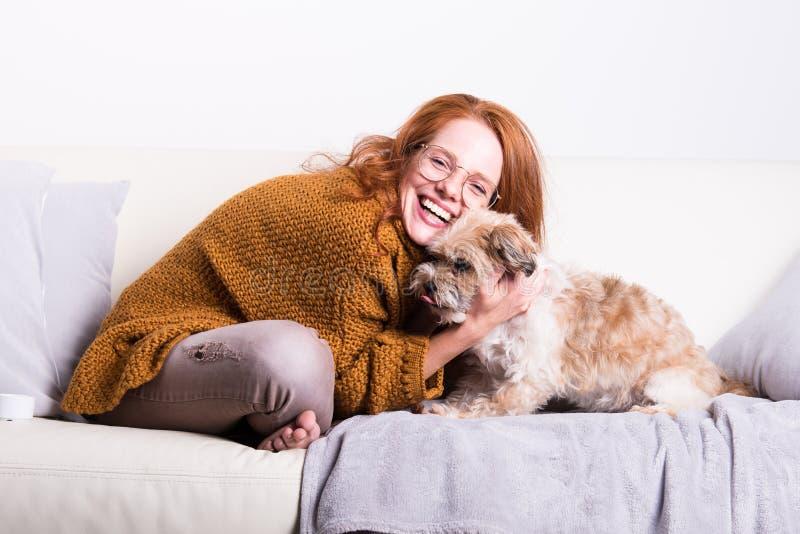 Härlig rödhårig kvinna med hennes hund på soffan royaltyfri bild