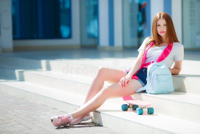 Härlig rödhårig kvinna som poserar med en skateboard arkivfoto