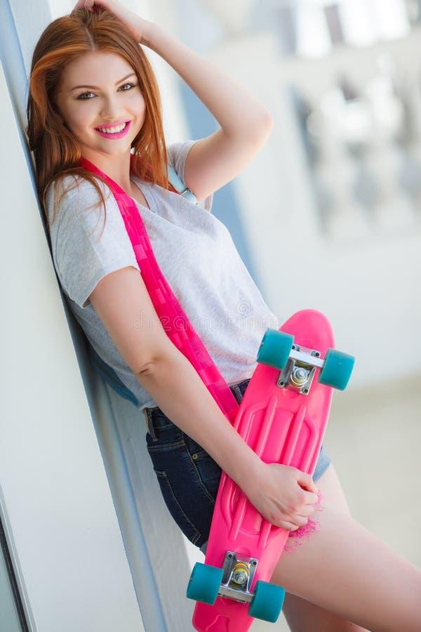 Härlig rödhårig kvinna som poserar med en skateboard arkivbilder