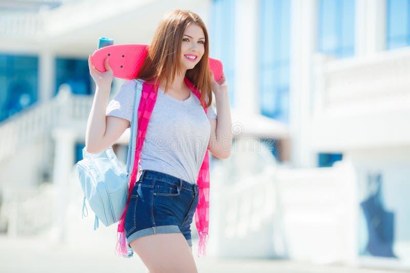 Härlig rödhårig kvinna som poserar med en skateboard royaltyfria foton