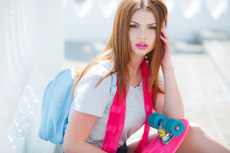 Härlig rödhårig kvinna som poserar med en skateboard arkivbild