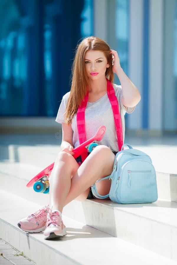 Härlig rödhårig kvinna som poserar med en skateboard royaltyfri bild
