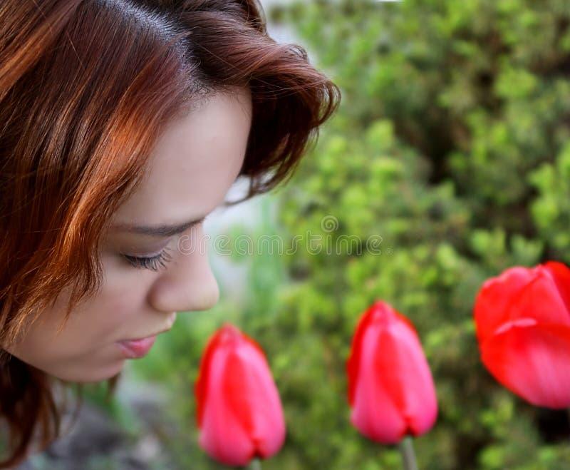 Härlig rödhårig man som luktar tulpan i en trädgård fotografering för bildbyråer