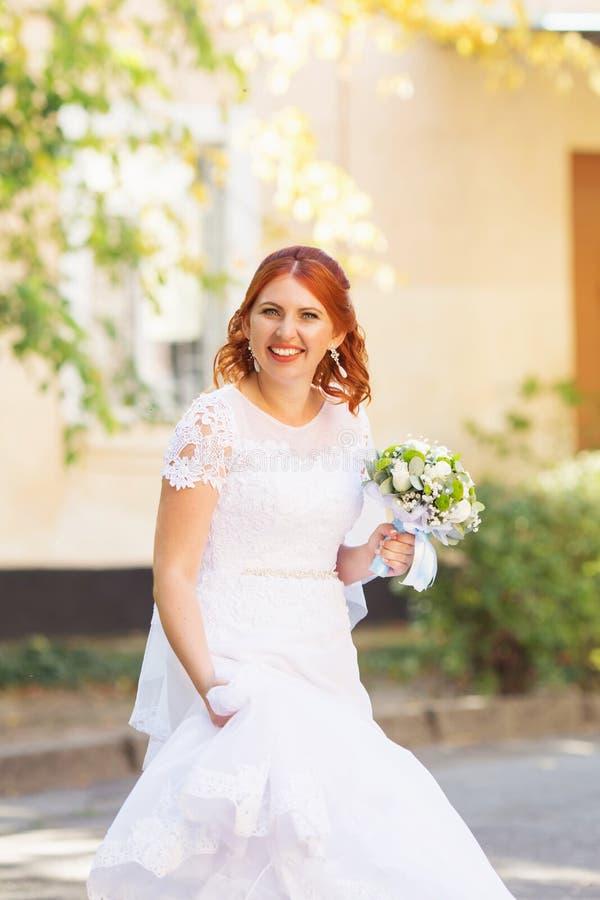 Härlig rödhårig manbrud med den utomhus- buketten Lycklig brudjumpin fotografering för bildbyråer