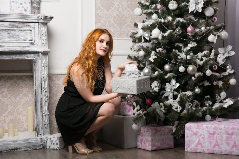 Härlig rödhårig ung kvinna med en gåva bredvid julgranen arkivfoton