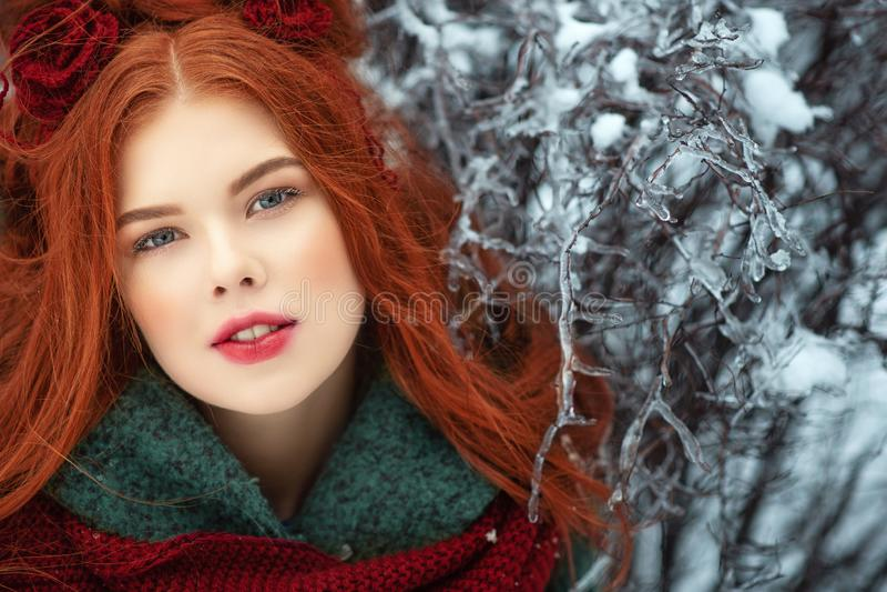 Härlig rödhårig ung kvinna med perfekt hud och att utgöra att posera på snöig och iskall bakgrund royaltyfri foto