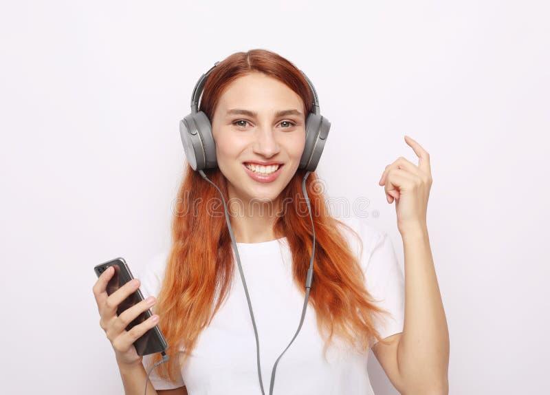 Härlig redhairkvinna i hörlurar som lyssnar till musik arkivfoton
