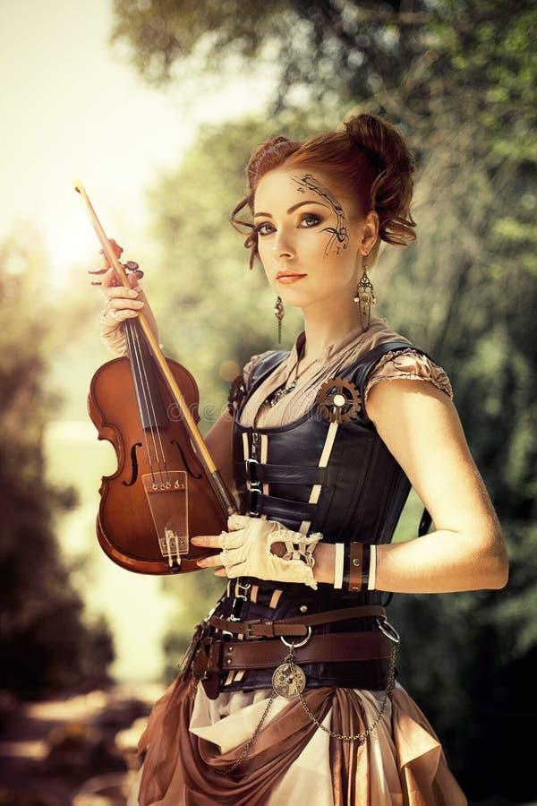 Härlig redhairkvinna med kroppkonst på hennes hållande fiol för framsida arkivfoton