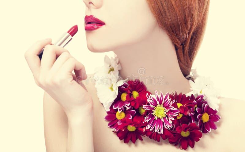 Härlig redheadflicka med blommainnehavläppstift arkivbild