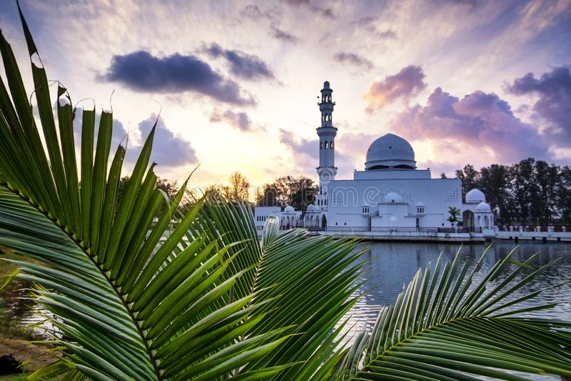 Härlig reflexion av den Tengku Tengah Zaharah moskén över soluppgångbakgrund, arkivbild