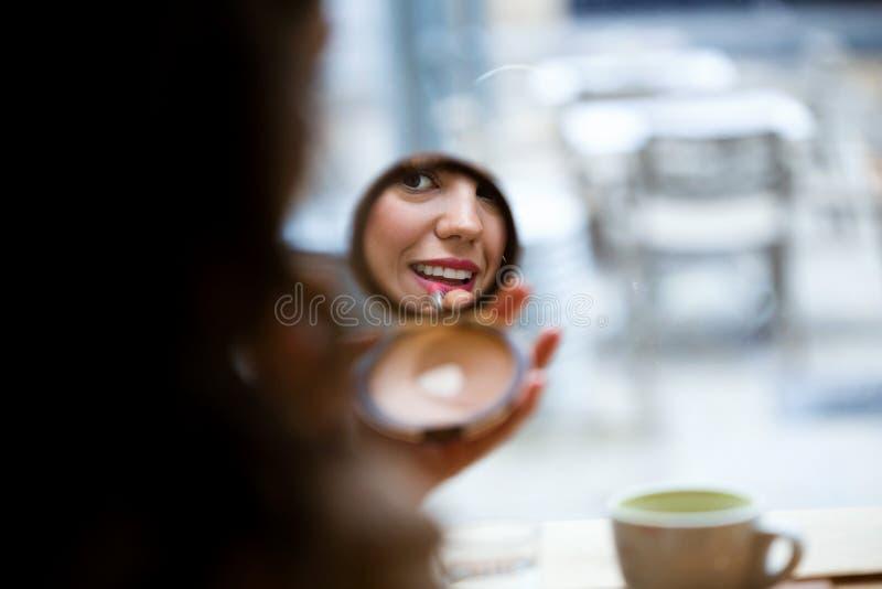 Härlig reflexion för ung kvinna som gör smink nära spegeln i coffee shop arkivbilder