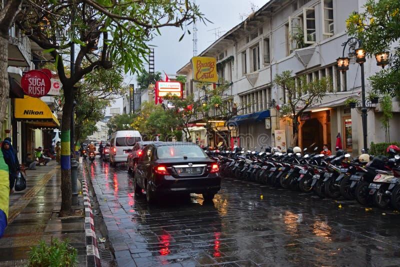 Härlig reflexion på den Braga gatan på Bandung, Indonesien under sen afton för regnig dag royaltyfri foto