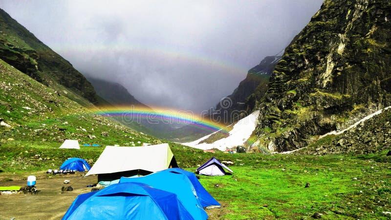 Härlig regnbåge, berg och snö, molnigt väder, campa tält arkivfoto