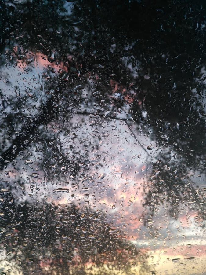Härlig regnig solnedgång utanför mitt bilfönster arkivbild