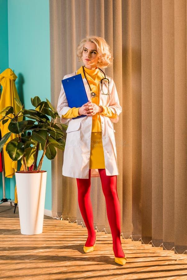 härlig retro utformad doktor, i färgrik skrivplatta och att se för klänninginnehav bort arkivfoto