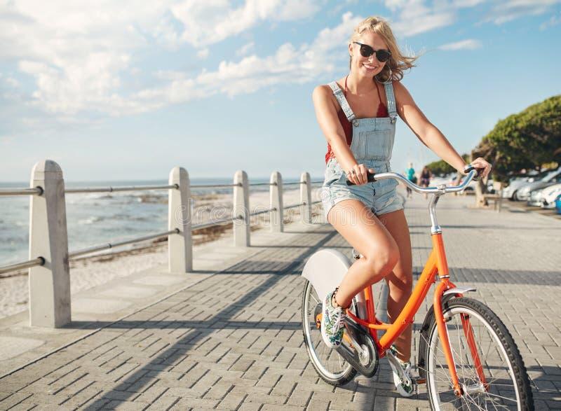 Härlig ridningcykel för ung kvinna på sjösidavägen royaltyfria bilder