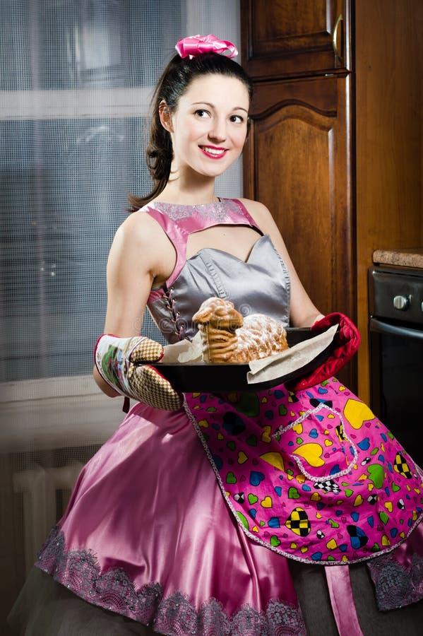 Härlig rolig ung utvikningsbrudkvinna, i lycklig le för klänning och för förkläde och baka smaskig kakastående royaltyfri foto