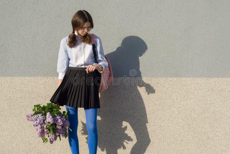 Härlig romantisk blick för tonårs- flicka på klockan, med buketten av lilan på grå väggbakgrund, kopieringsutrymme arkivfoto