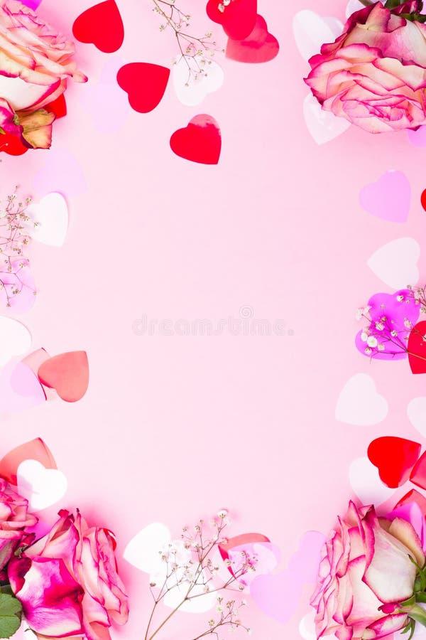Härlig rosa färgros, dekorativa konfettihjärtor och rosa band på rosa valentindagbakgrund royaltyfria foton